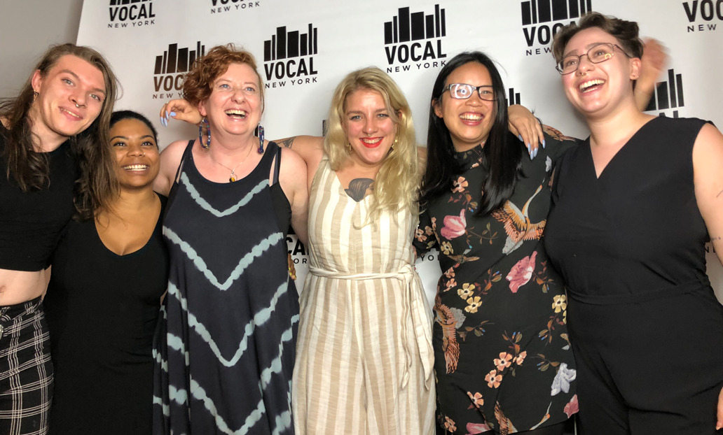 a group of NHRC staff smiling together in front of a Vocal New York backdrop.